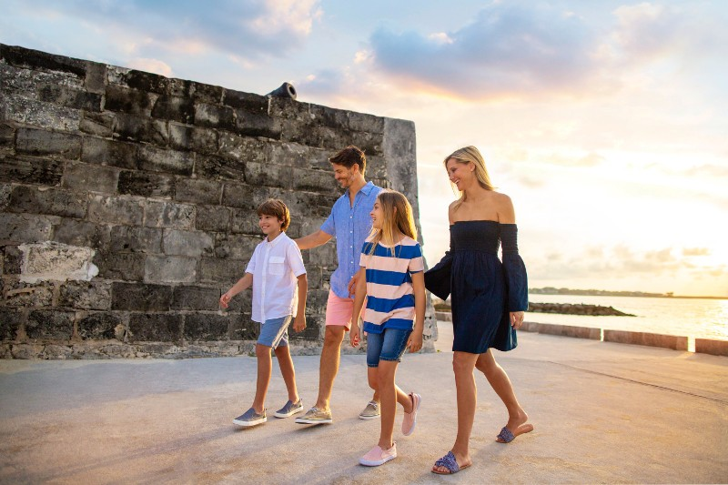 A family walks past a historic fort in Nassau, Bahamas.