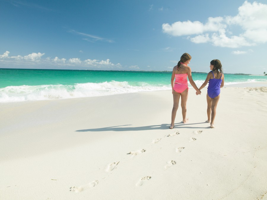 Two young girls hold hands and walk on a beach in The Bahamas.