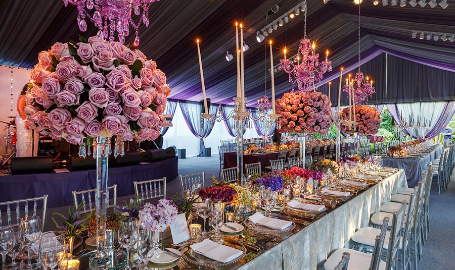 Dramatic table decor, chandeliers and rose bouquets decorate a wedding reception in Nassau Paradise Island, Bahamas