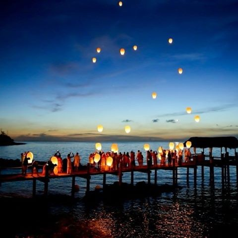 Wedding guests let lanterns float into the clear evening sky at a Bahamas destination wedding.