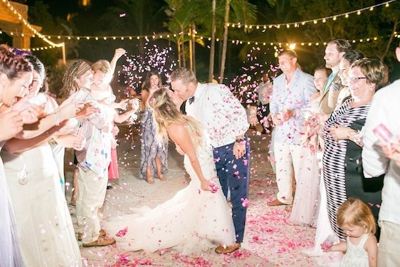 Newlyweds embrace surrounded by loved ones at their Atlantis wedding in the Bahamas