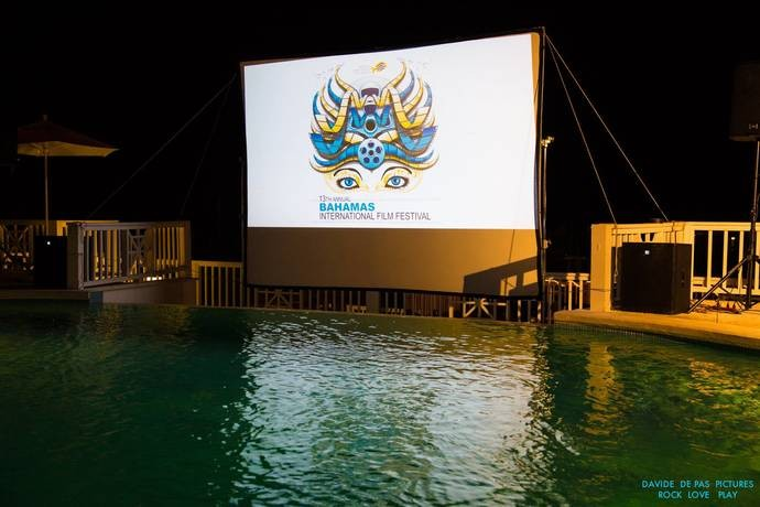 A movies screen with the Bahamas International Film Festival logo is set up next to a pool.