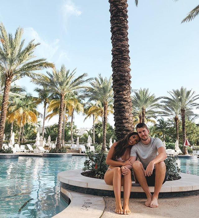 A couple pose for a photo next to a pool.