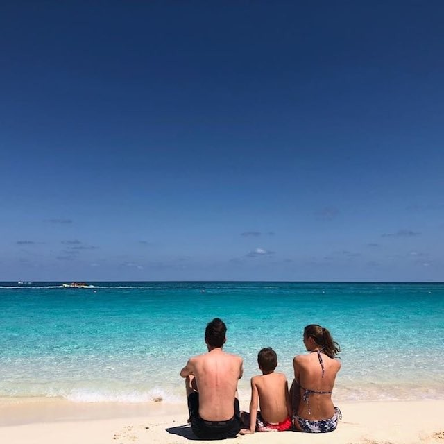 A family of three enjoy the view while sitting on a white sand beach in Nassau, Bahamas.