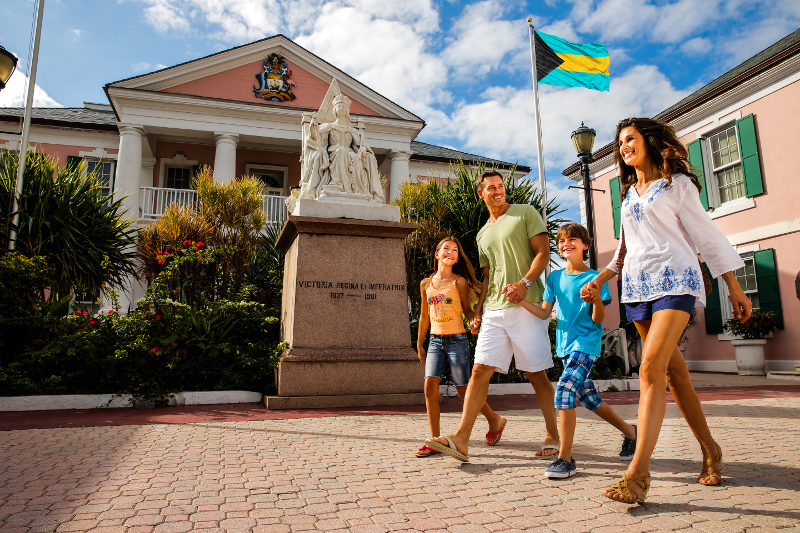 A family of four walks through Parliament Square on a sunny day in Nassau, Bahamas.