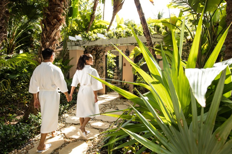A couple walking in robes outside a spa in Nassau Paradise Island