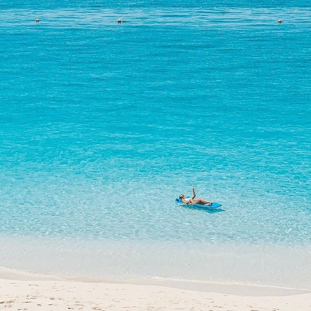 A woman floats in the tropical turquoise waters of Nassau Paradise Island.
