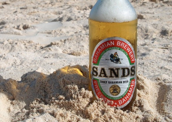 A bottle of Sands beer sticks out of the sand on a Bahamas beach.