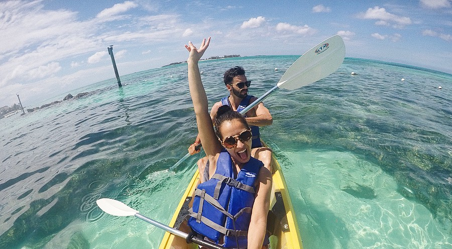 A couple take a selfie while kayaking the crystal clear waters of The Bahamas.