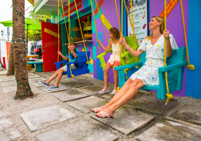 A family poses in swings outside a colorful building in The Bahamas.