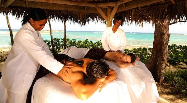 A man and woman enjoy a couples massage on the beach in The Bahamas.