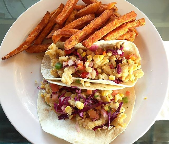 Shrimp tacos with sweet potato fries on a white plate.
