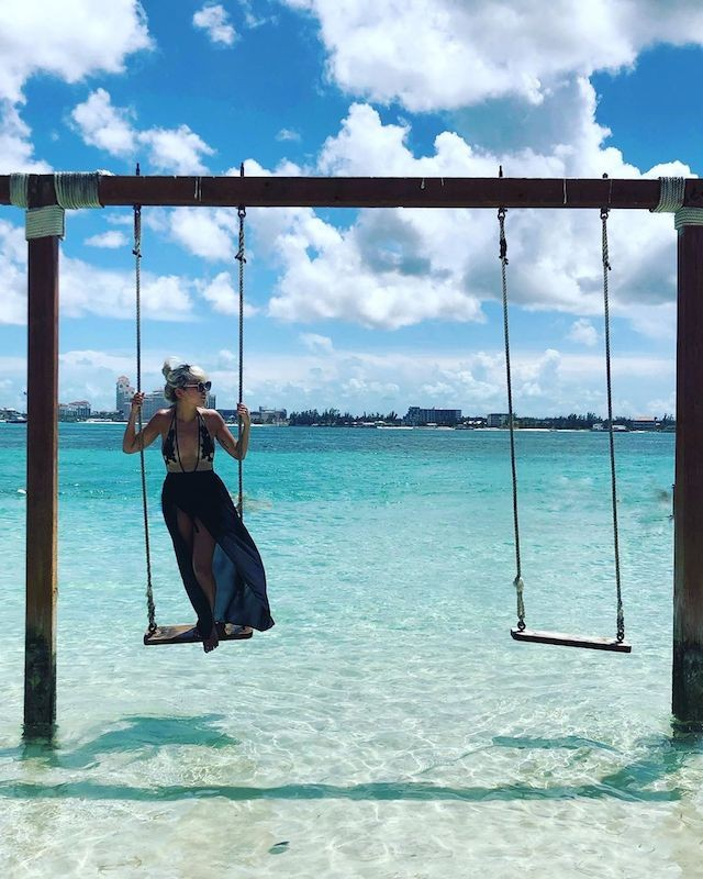 A woman stands on a swing set in the clear tropical waters of The Bahamas