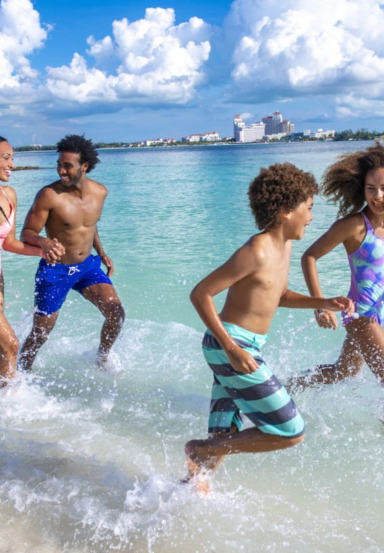 A family of fun splashes in the waves on a Bahamas beach.