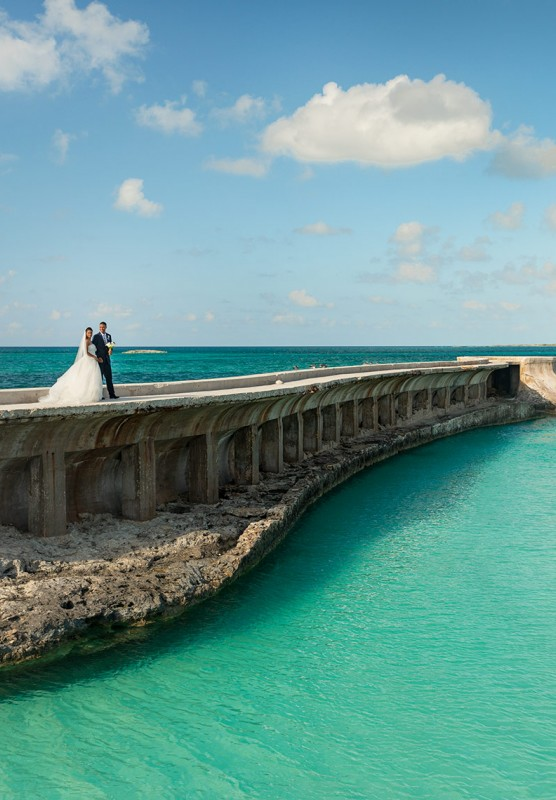 A bride and groom stand on a boardwalk that runs alongside a small river