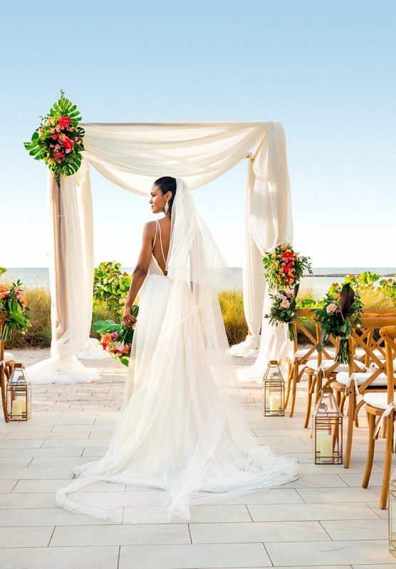 A bride walks down the aisle at her outdoor Bahamian wedding.