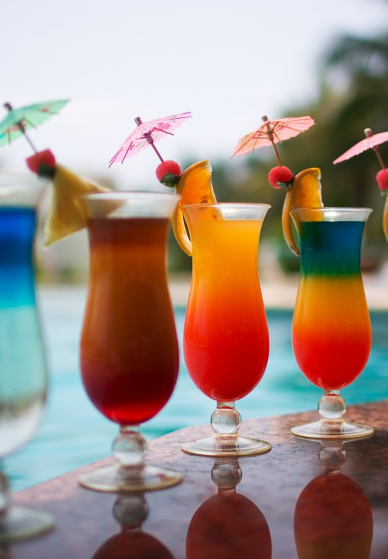 A row of colorful tropical drinks by a pool