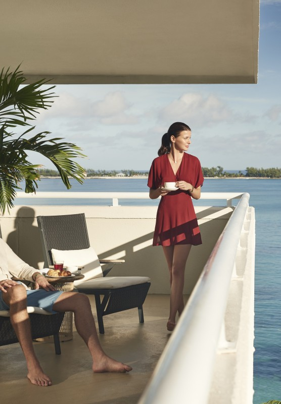 A couple relax on a balcony that overlooks the ocean