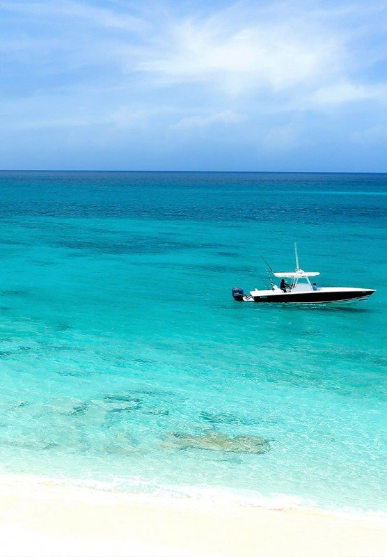 A small motor boat sailing through clear turquoise waters on a beautiful day.