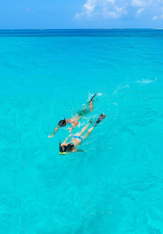 A couple snorkels through bright blue tropical waters.
