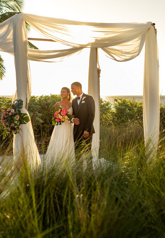 Couple getting married under canopy outside in the grass