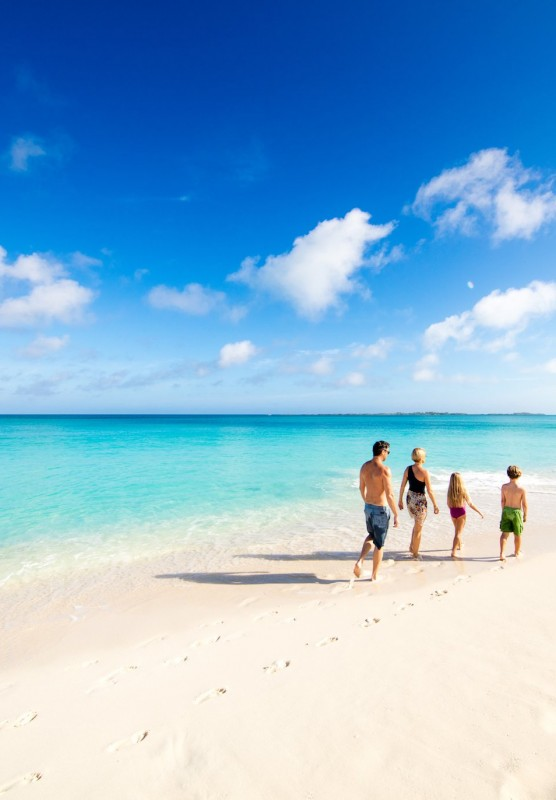 Family walking along the water on a beautiful white sandy beach