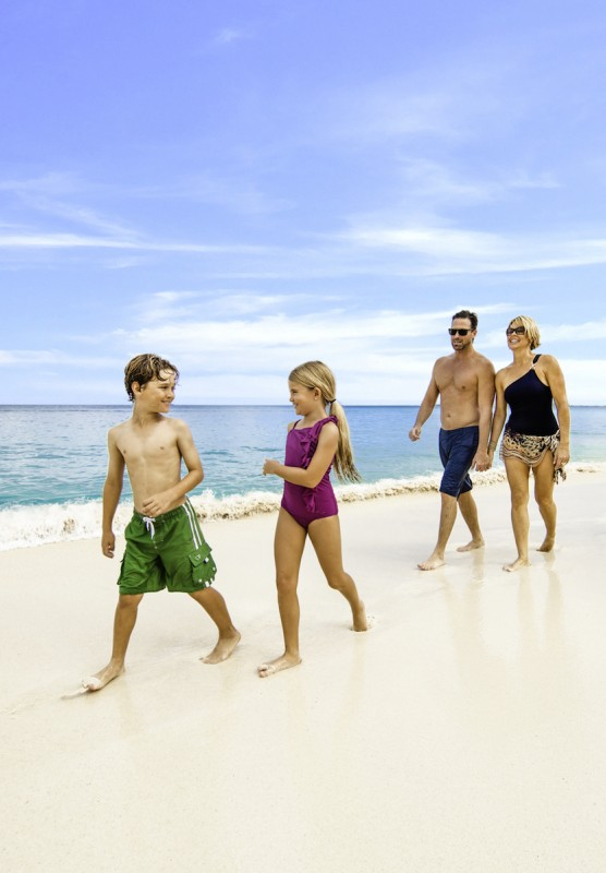 Two children, their parents, and grandparents walk on a Bahamas beach.