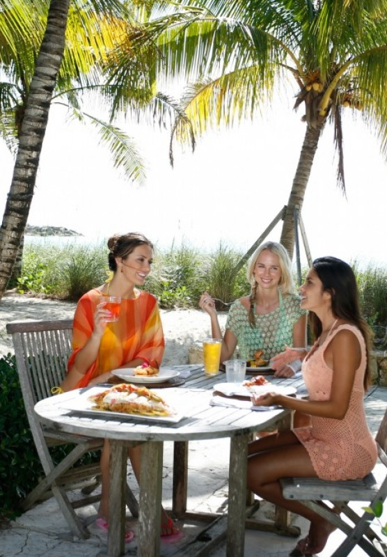 Three women dine at a table surrounded by palm trees in The Bahamas.