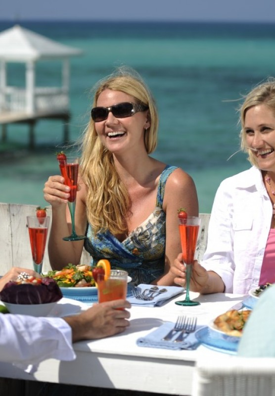 A group of friends enjoy a outdoors at a beachside establishment in Nassau, Bahamas.