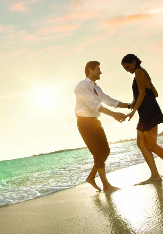 Couple dancing on the beach in front of sunset