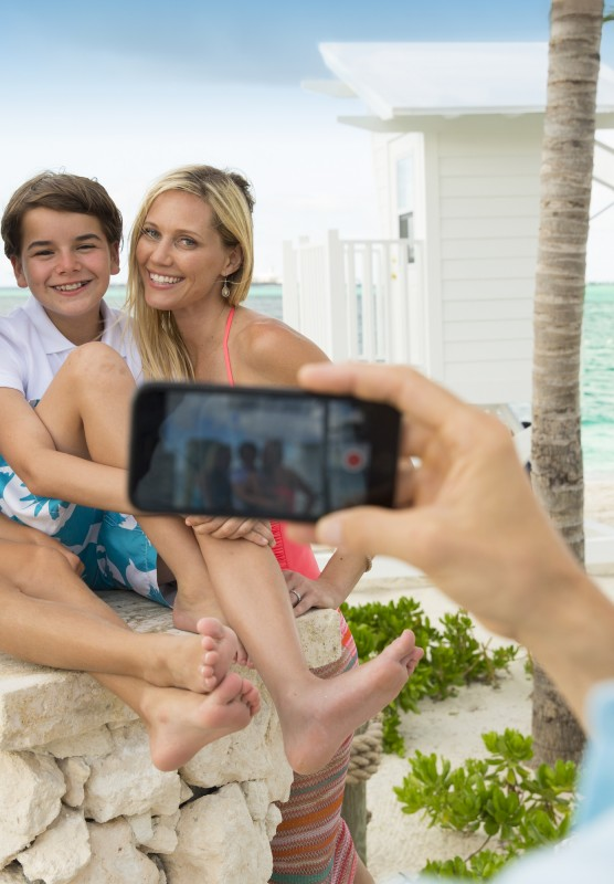 A visitor takes a photo of their family with their mobile phone.