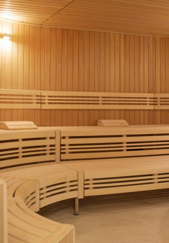 A round wooden sauna room with long benches