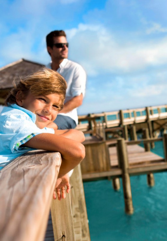 Boy and man lean over a pier and look out at blue water