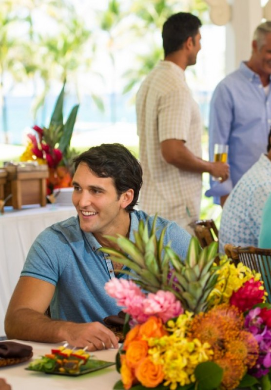 A group of friends enjoys a Bahamian-themed party at a tropically decorated table.