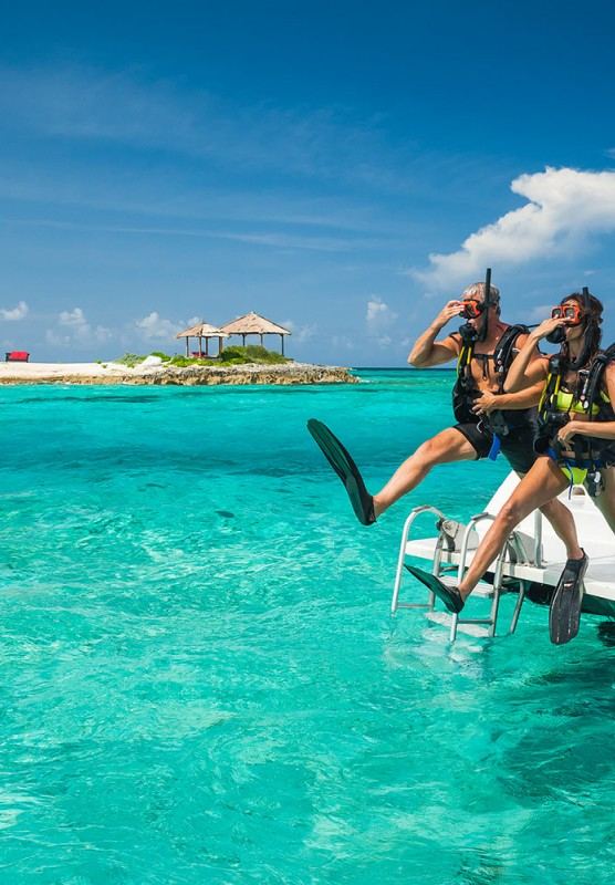 A couple in snorkeling gear jumps into the water at Sandals Royal Bahamian's Offshore Island.