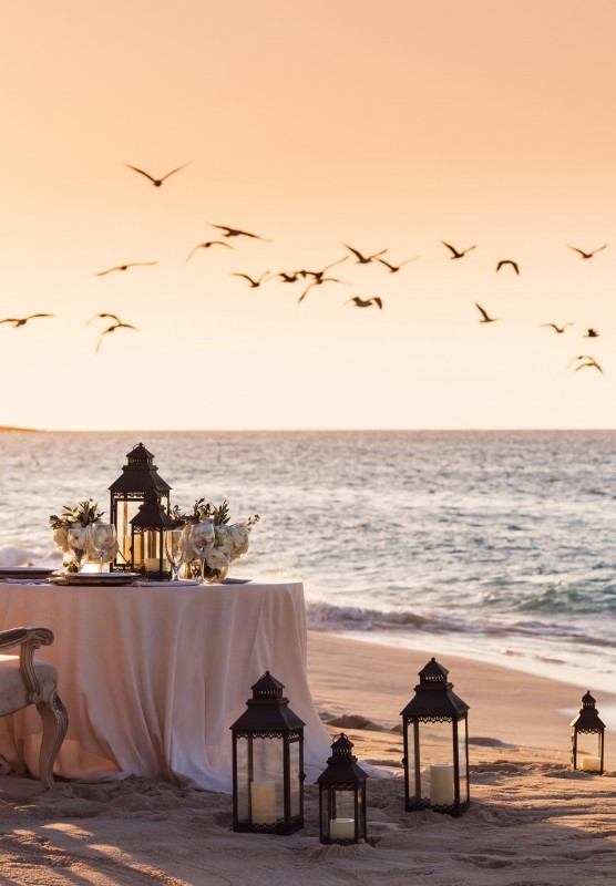 A table and lanterns set-up on the beach