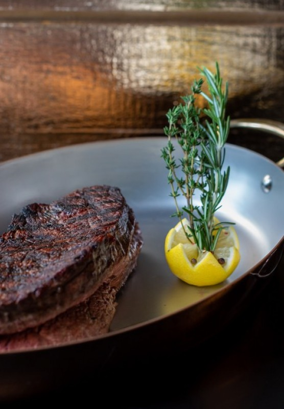 A steak and lemon on a pan