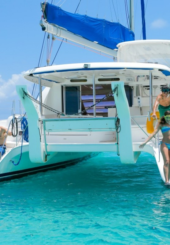 A couple and family prepare to jump off the back of a catamaran into turquoise Bahamas waters.