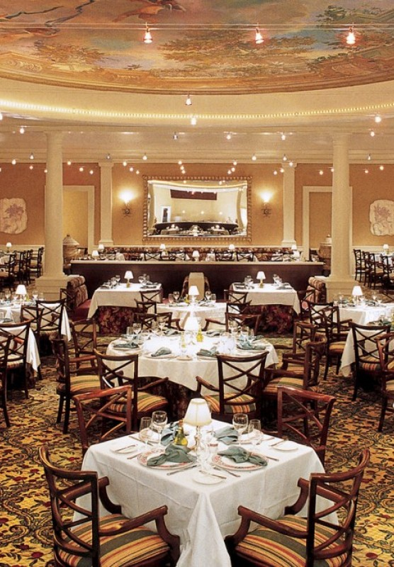 Tables are set for dinner in a large dining area with white pillars and an intricately painted ceiling.