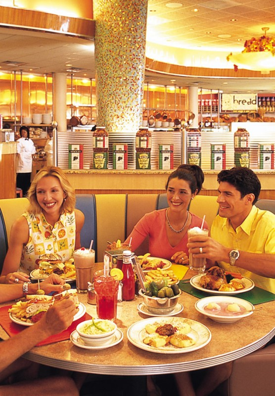 Two men and two women sitting at a round table filled with food in a brightly lit restaurant.