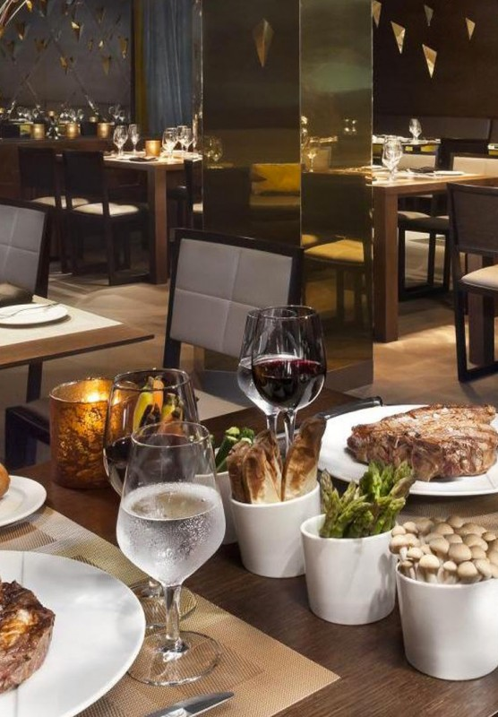 Steaks, asparagus, mushroom, bread and wine set on a table in an empty, modern restaurant.