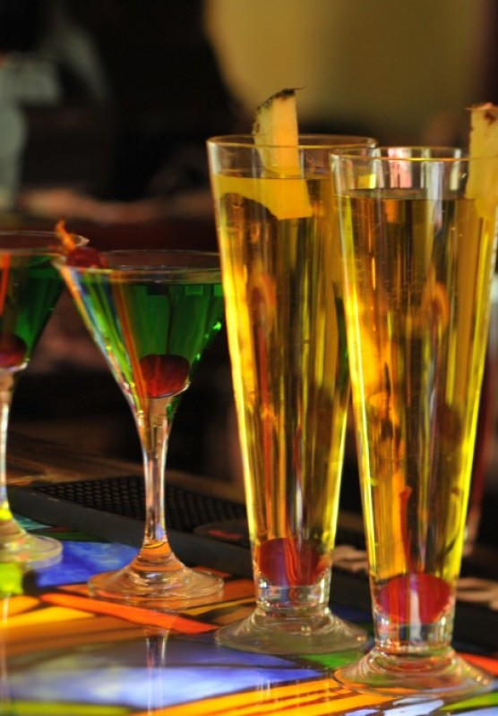 A row of tropical cocktails sits on a colorful bar.