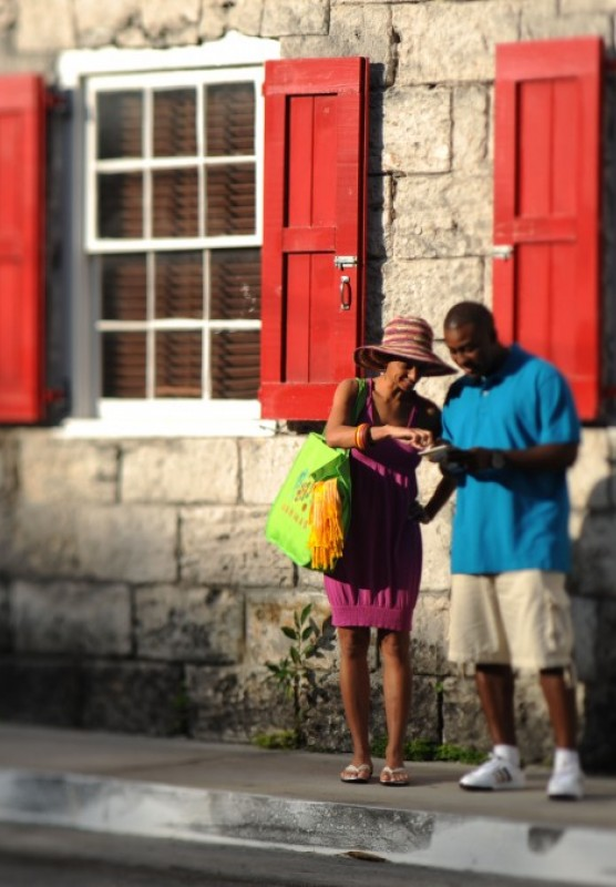 A couple stops to look at a map outside a historic building in Nassau Bahamas.