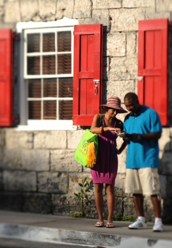 A couple look at a map outside a historic Bahamas building with red shutters.