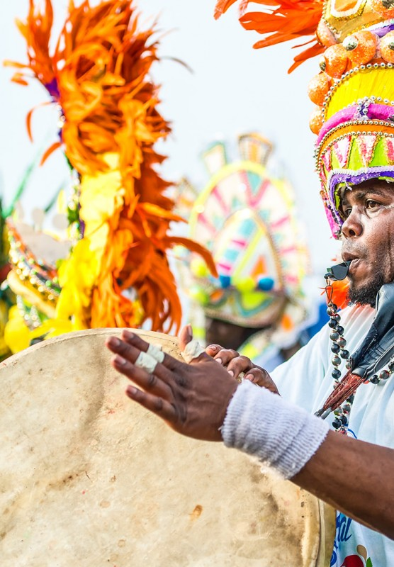 A man in a brightly colored headdress blowing a whistle and playing a drum at Carnival.