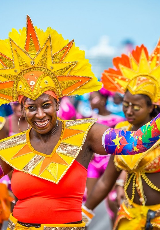 Women walking in brightly colored outfits for Carnival.