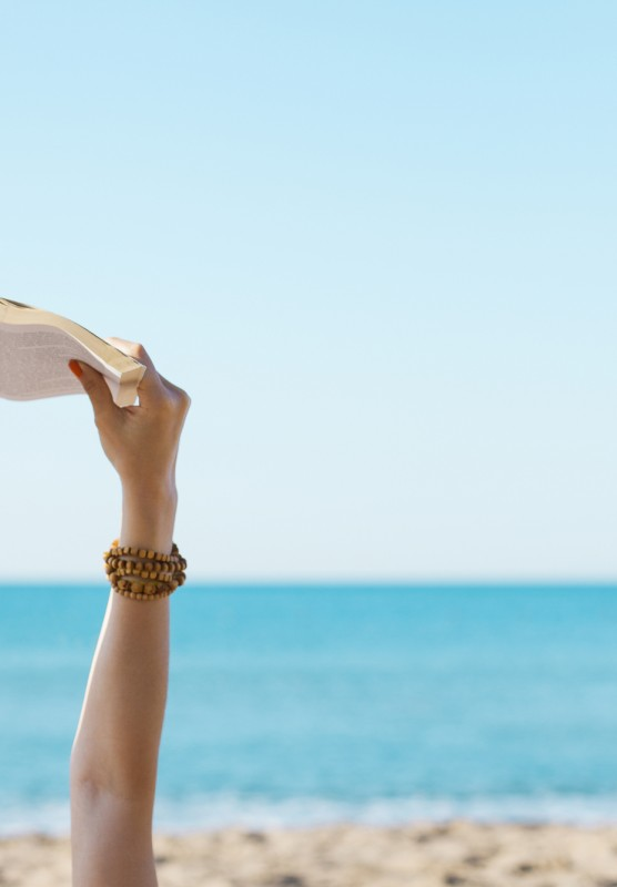 A woman holds a book up to read it on the beach.