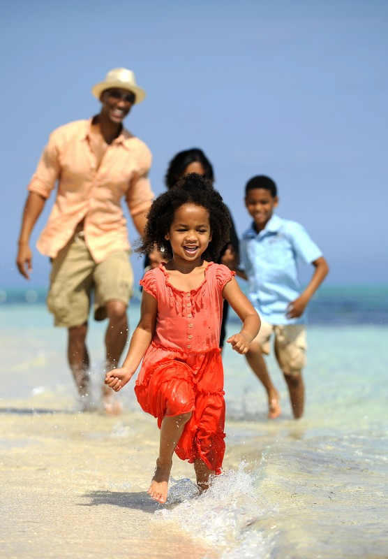 Little girl running in the water with family running behind her