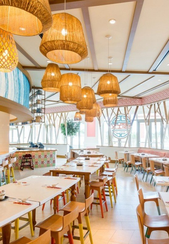 The interior of a restaurant with long wooden tables and decorative hanging light fixtures.