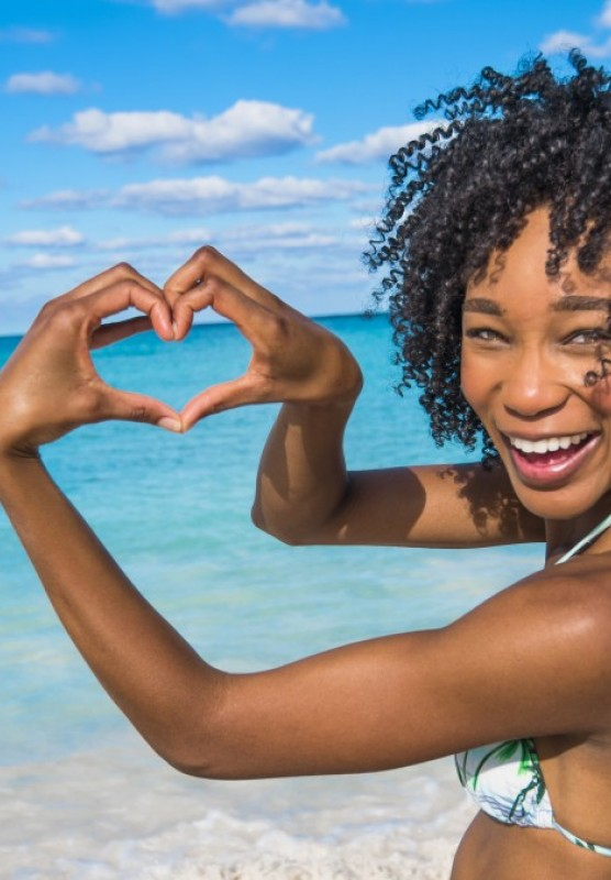 A woman smiles and makes a heart with her hands on the shores of Nassau Paradise Island.